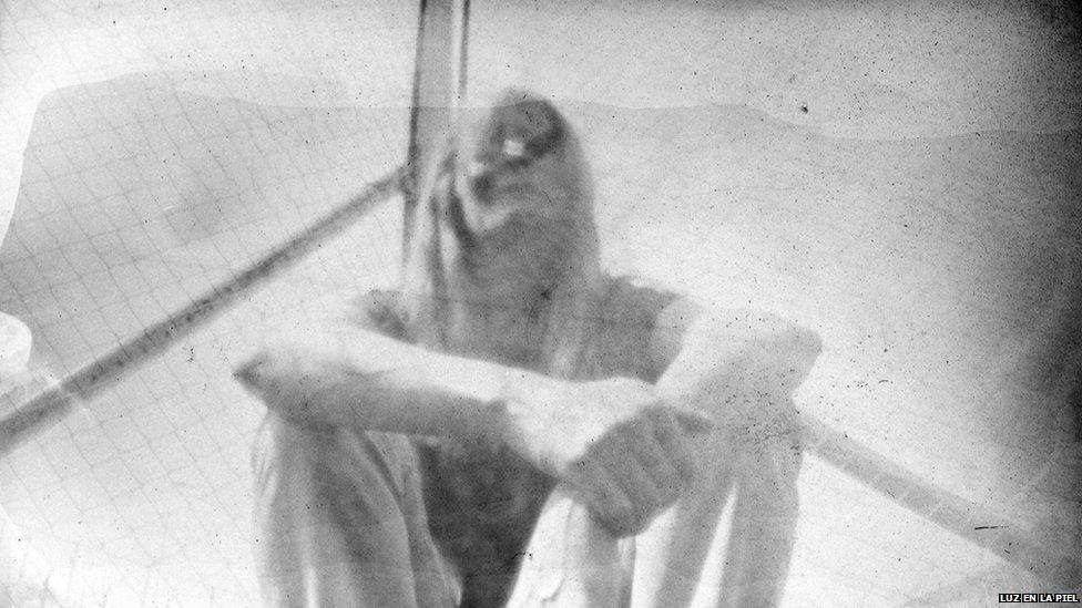 A pinhole photograph shows a woman