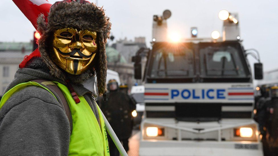 """A masked protestor stands in front of a police vehicle in Paris on 5 January 2019, during a rally by yellow vest """"Gilets Jaunes"""" anti-government protesters"""