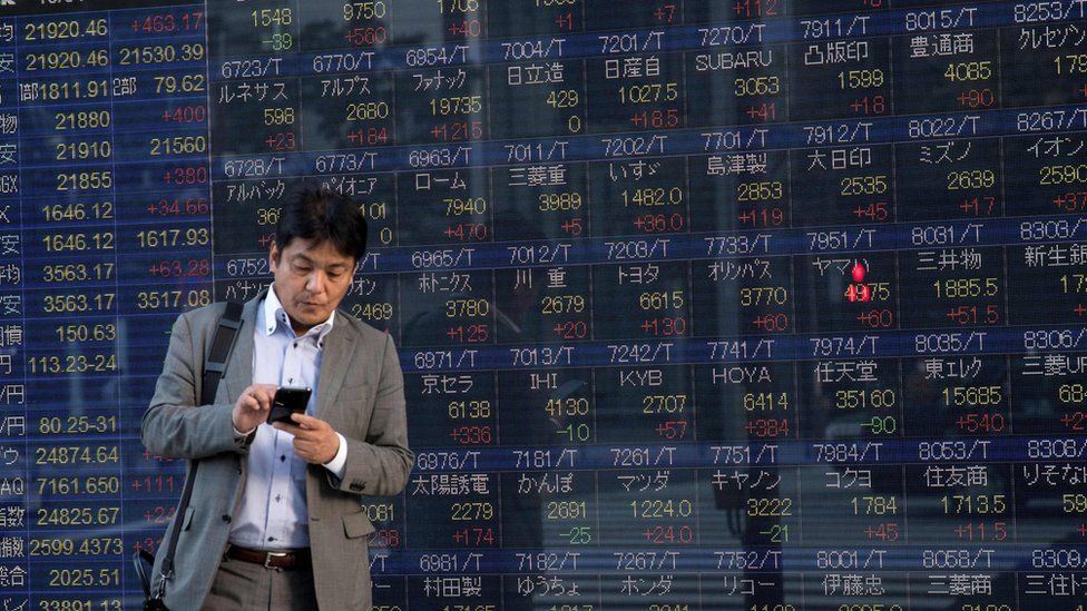Man stands in front of stock boards in Japan