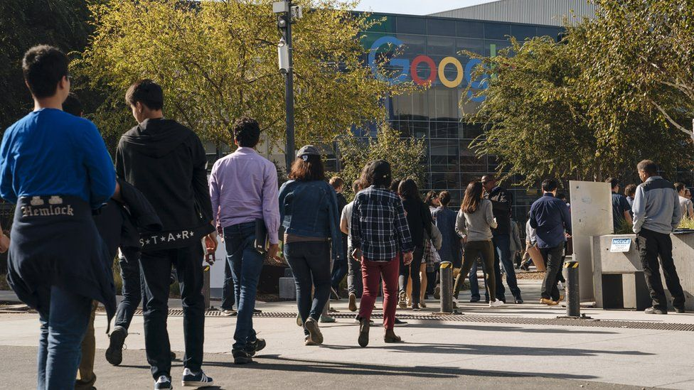 Google employees stage a walkout in November 2018 over sexual misconduct allegations, with the headquarters visible in the background