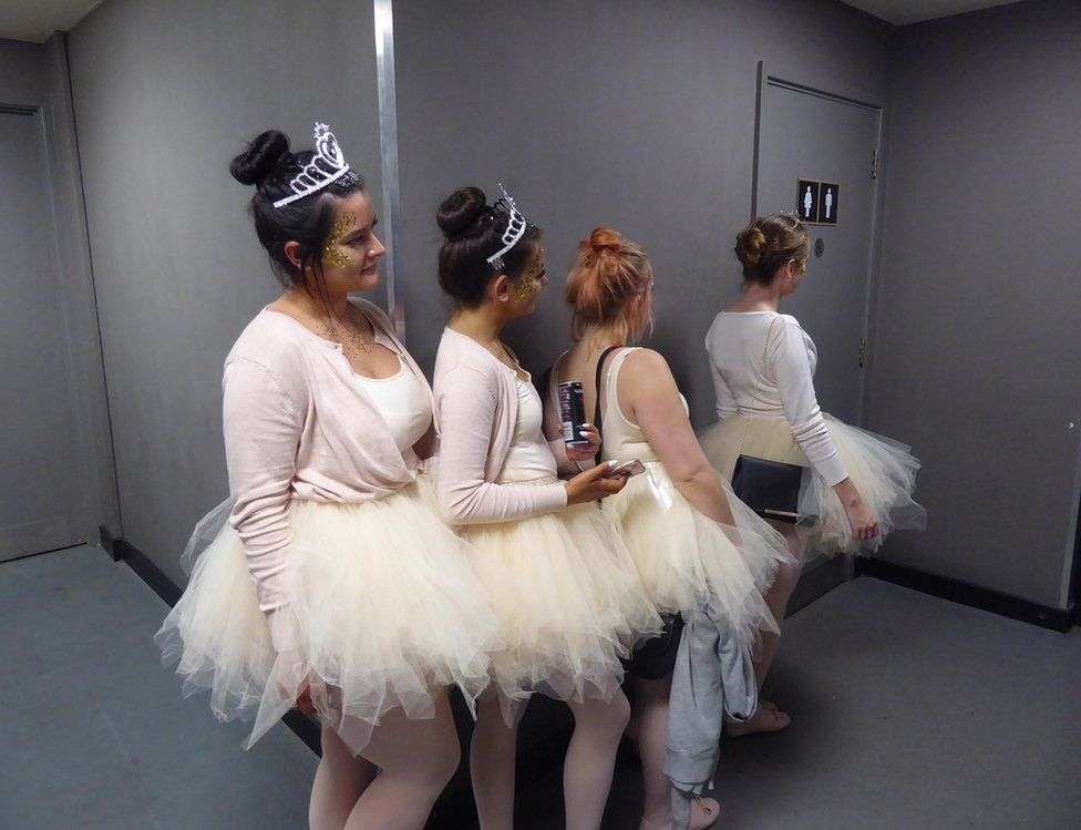 Ballerinas waiting in a queue for the loo