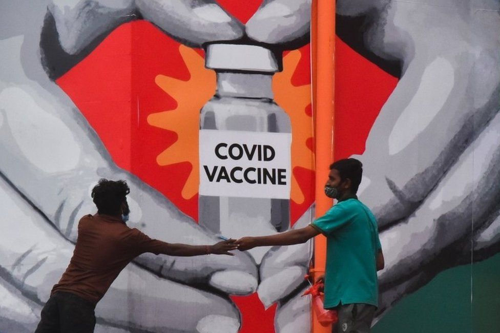 indian workers give final touches to a huge mural made on a wall outside the Tambaram railway station to promote awareness on the Covid-19 coronavirus disease vaccination in Chennai, India, 04 July 2021