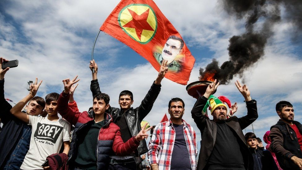 Kurdish men hold up a flag with a picture of the jailed PKK leader Abdullah Ocalan during Newroz celebrations in Diyarbakir