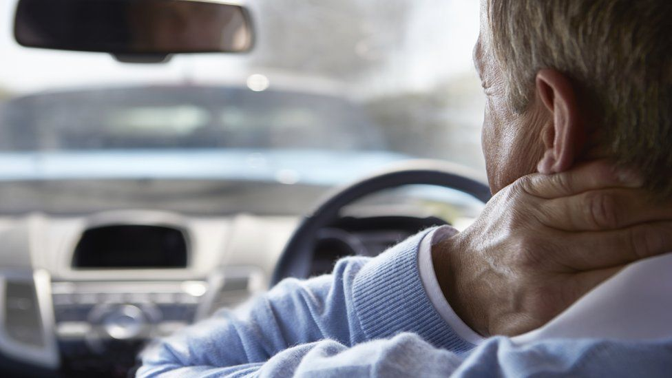 Driver holds his neck, apparently in pain, while sat at wheel of car