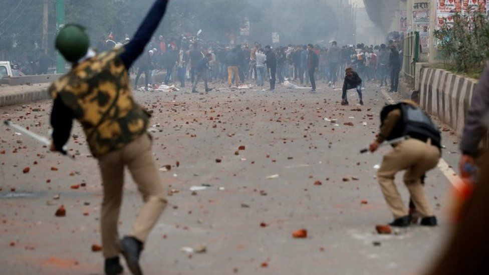 A riot police officer throws a piece of brick towards demonstrators during a protest against a new citizenship law in Seelampur, Delhi