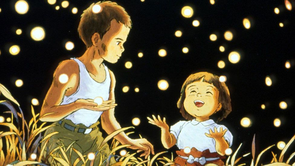 A still from Grave of the Fireflies showing the main character and his sister watching fireflies