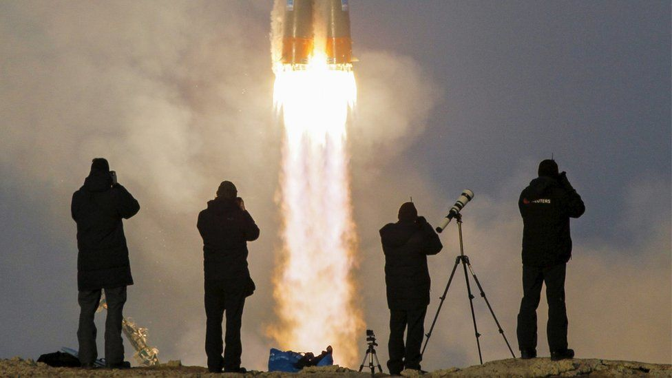 Photographers take pictures as the Soyuz TMA-19M spacecraft