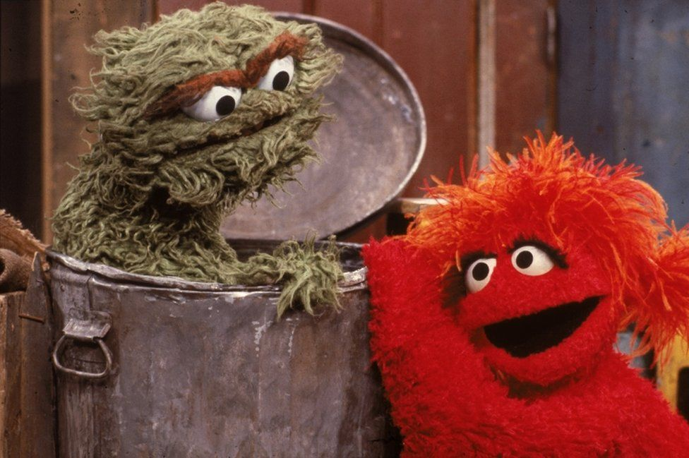 """A red muppet visits Oscar the Grouch, inside his garbage can, in a scene from """"Sesame Street"""" in the 1980s."""