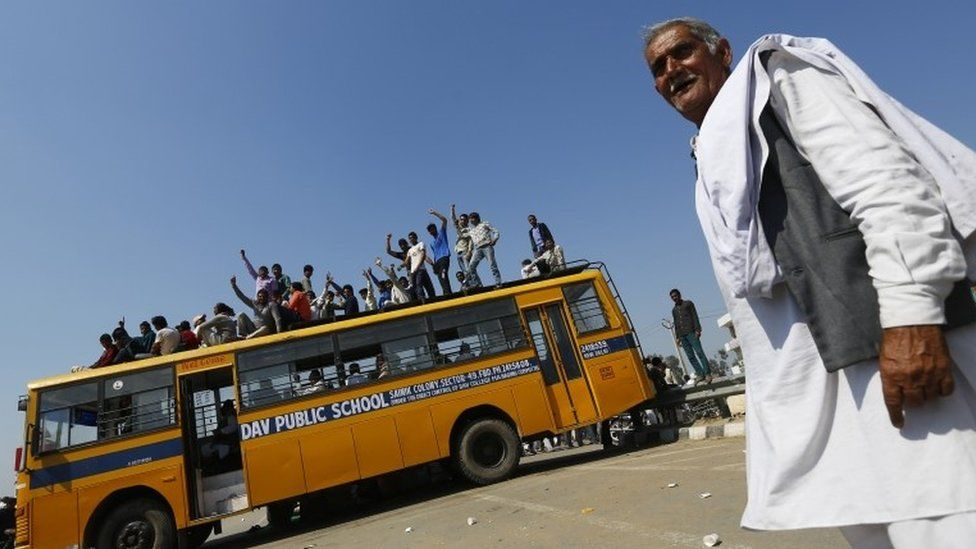 Demonstrators from the Jat community sit on top of a school bus as they block the Delhi-Haryana national highway during a protest at Sampla village in Haryana, India, February 22, 2016.