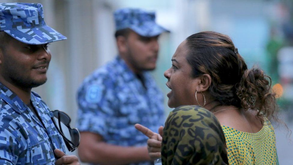 A Maldivian opposition activist argues with a policeman outside parliament in Male on March 27, 2017.
