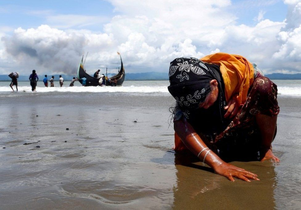 An exhausted Rohingya refugee woman touches the shore after crossing the Bangladesh-Myanmar border by boat through the Bay of Bengal, in Shah Porir Dwip, Bangladesh September 11, 2017.