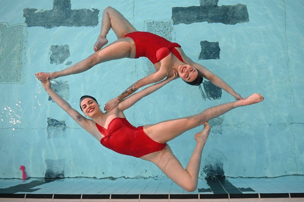 Members of Aquabatix, a synchronised swimming team practice at a swimming pool