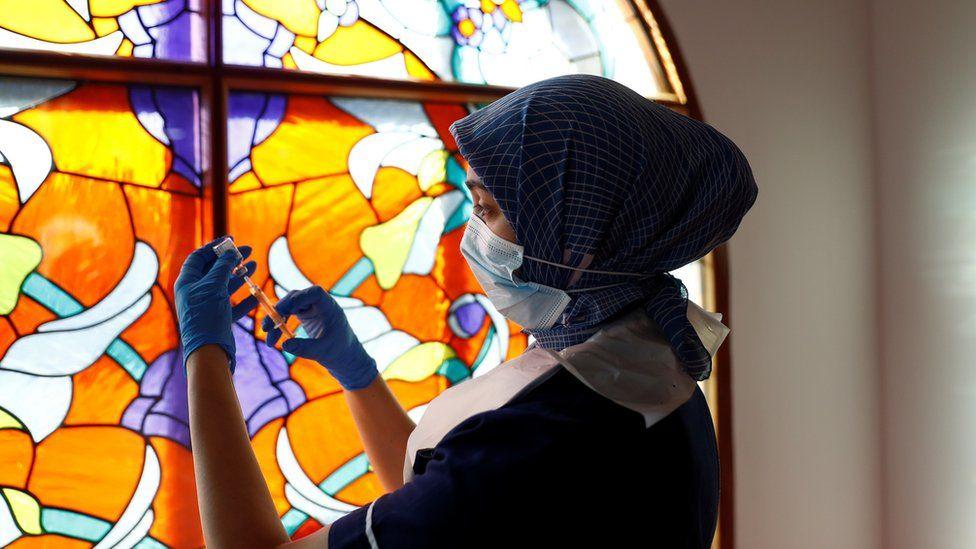 A woman prepares a dose of a coronavirus vaccine at Bradford Central Mosque