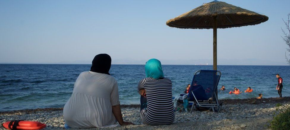 Women look on from the beach