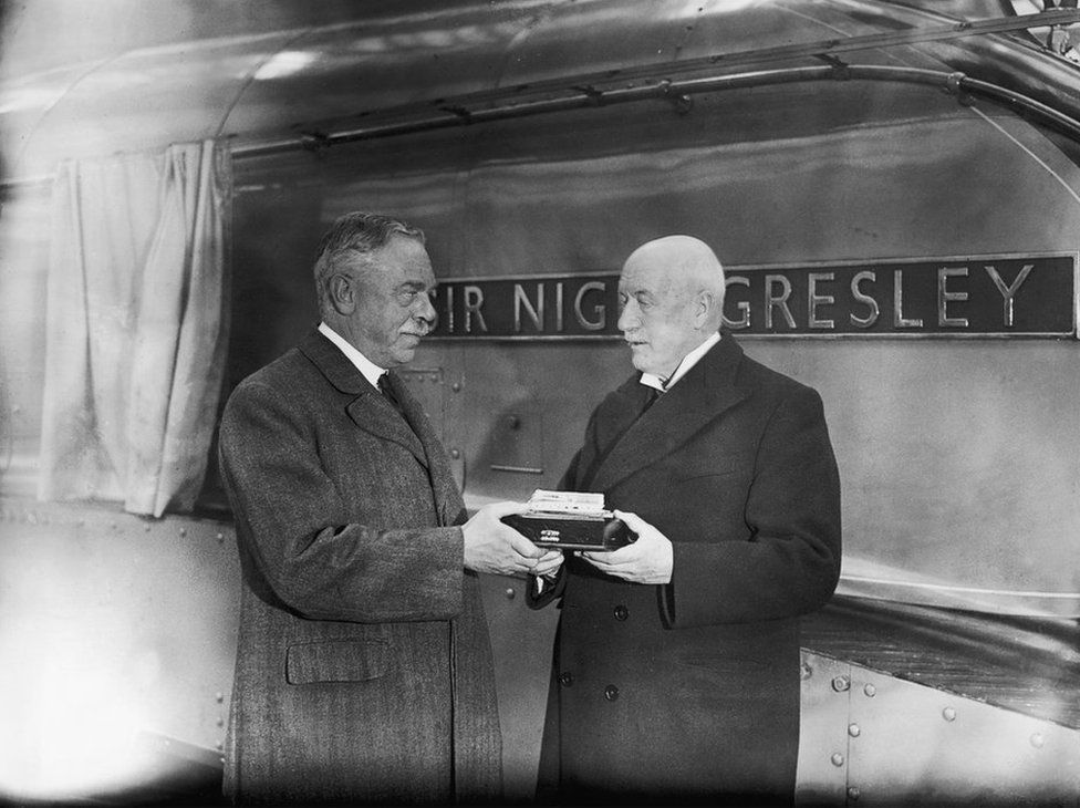 William Whitelaw presents railway engineer Sir Nigel Gresley with a silver model of the engine named after him, November 1937