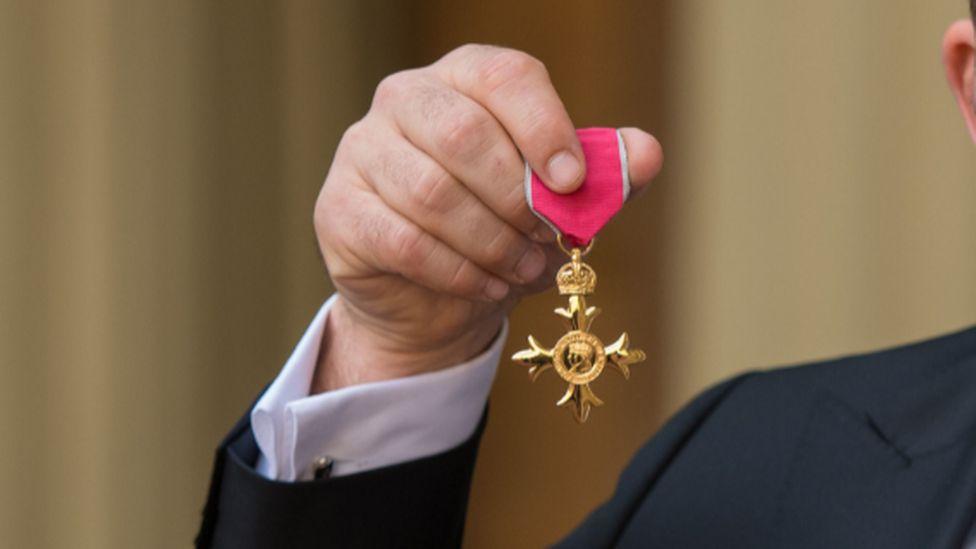 Man holding MBE medal