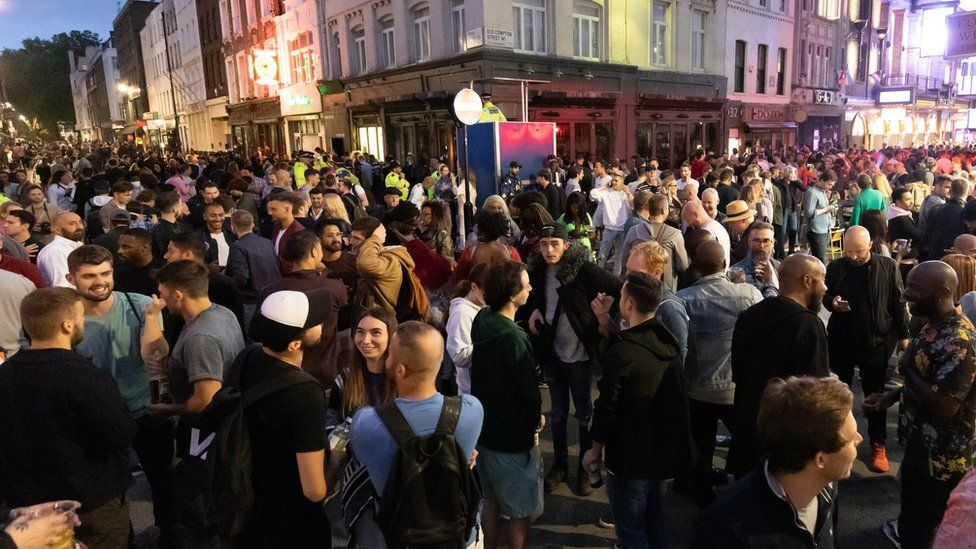 Revellers drink and socialise in the street in Soho, London