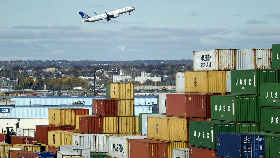 Plane flying over stack of containers