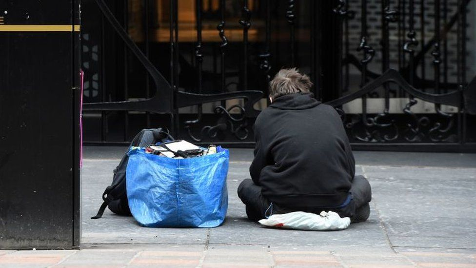 A homeless person sits in a Glasgow city centre street on March 27, 2020