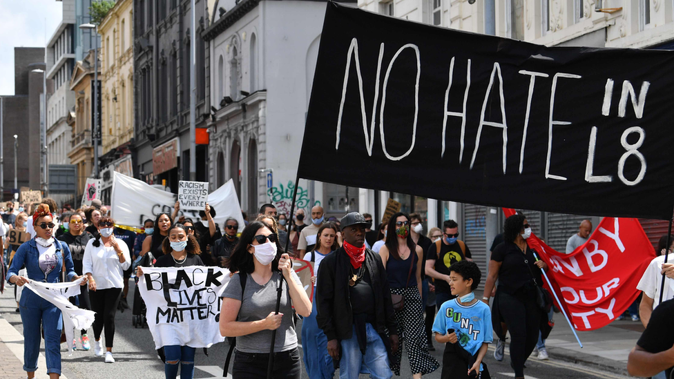 Demonstrators hold No hate in L8 banner