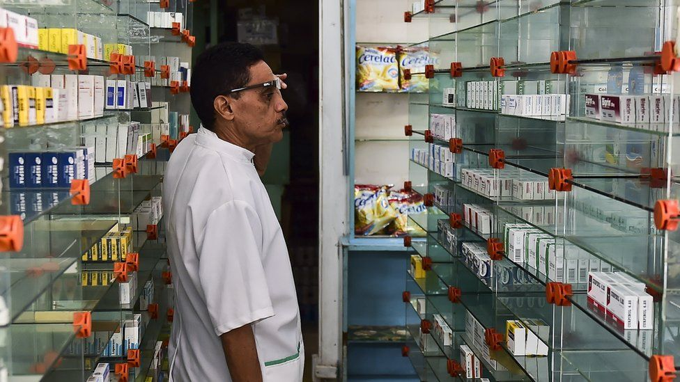 A worker of an empty pharmacy is pictured in Caracas on May 30, 2016