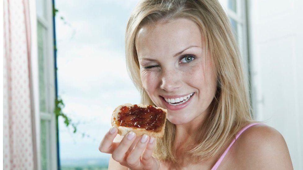 Woman eating jam sandwich
