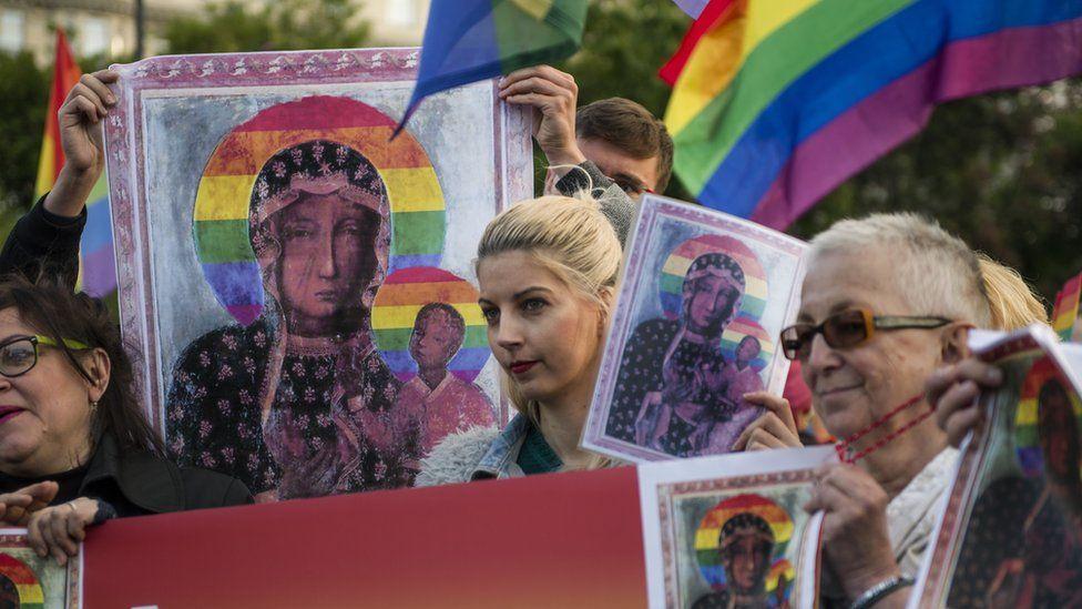 Demonstrators wave abundant copies of Ms Podlesna's poster alongside rainbow flags