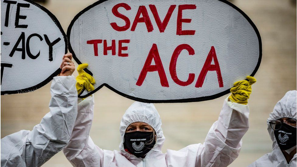 Protesters who support Obamacare stand outside the Supreme Court during the hearing