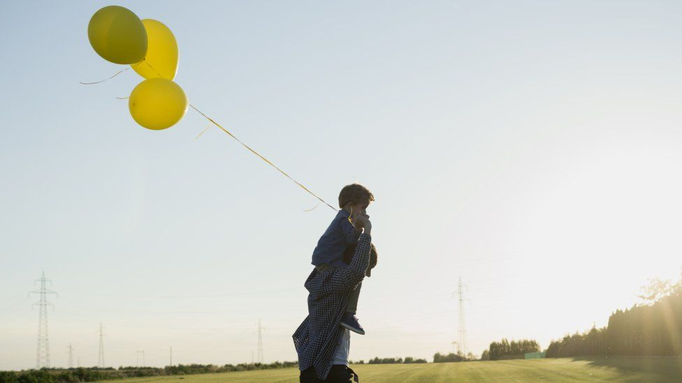 A man with a boy on his shoulders, holding balloons