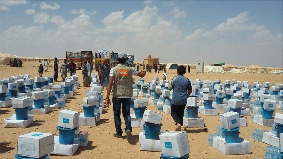 Members of the Norwegian Refugee Council hand out emergency kits to displaced people in western Iraq