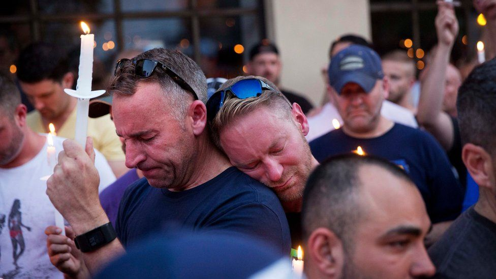 Paul Cox, right, leans on the shoulder of Brian Sullivan, as they observe a moment of silence during a vigil for a fatal shooting at an Orlando nightclub, Sunday, June 12, 2016, in Atlanta.