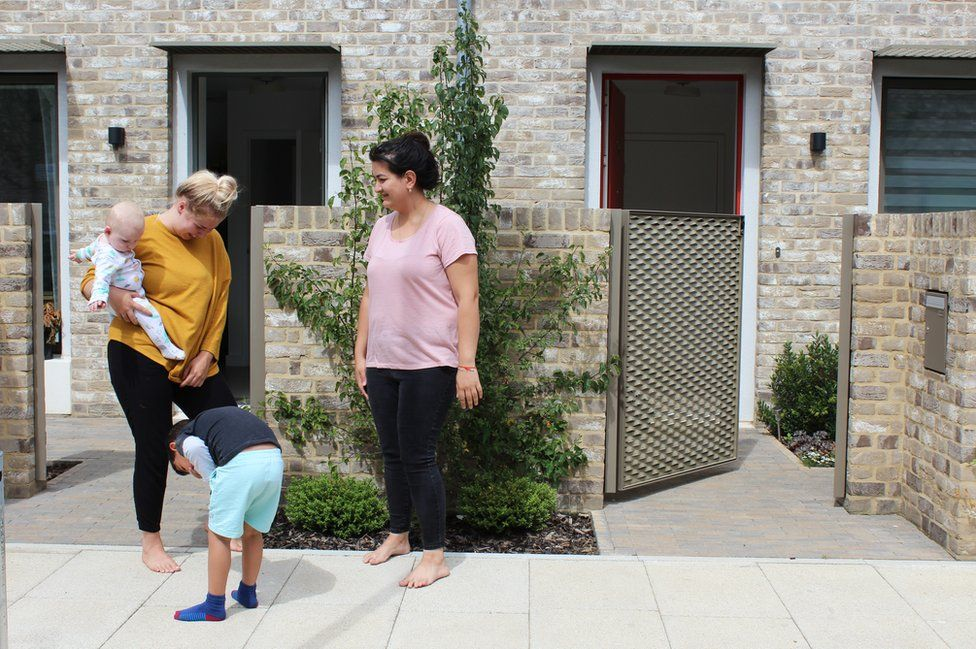 Two mothers and their children stand outside their houses