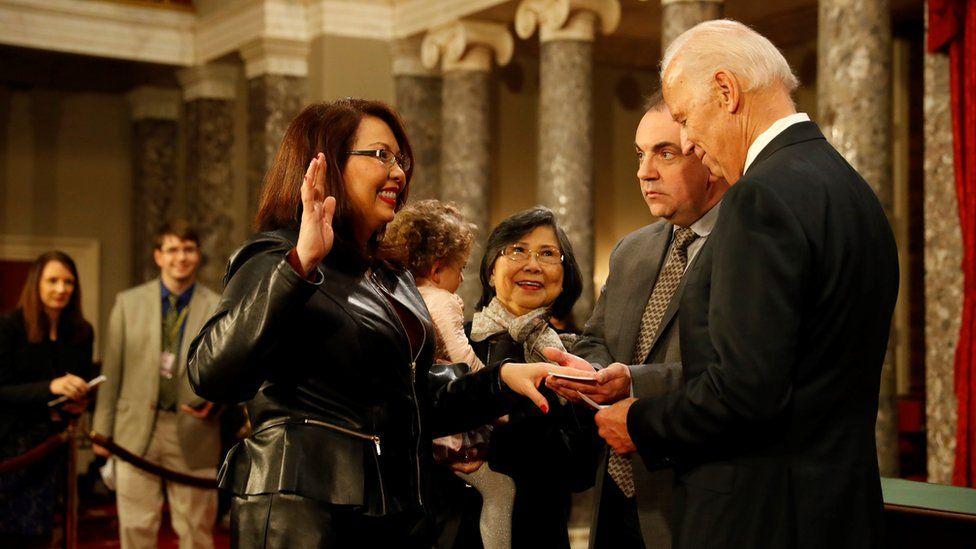 U.S. Sen. Tammy Duckworth (D-IL) participates in a reenacted swearing-in with U.S. Vice President Joe Biden