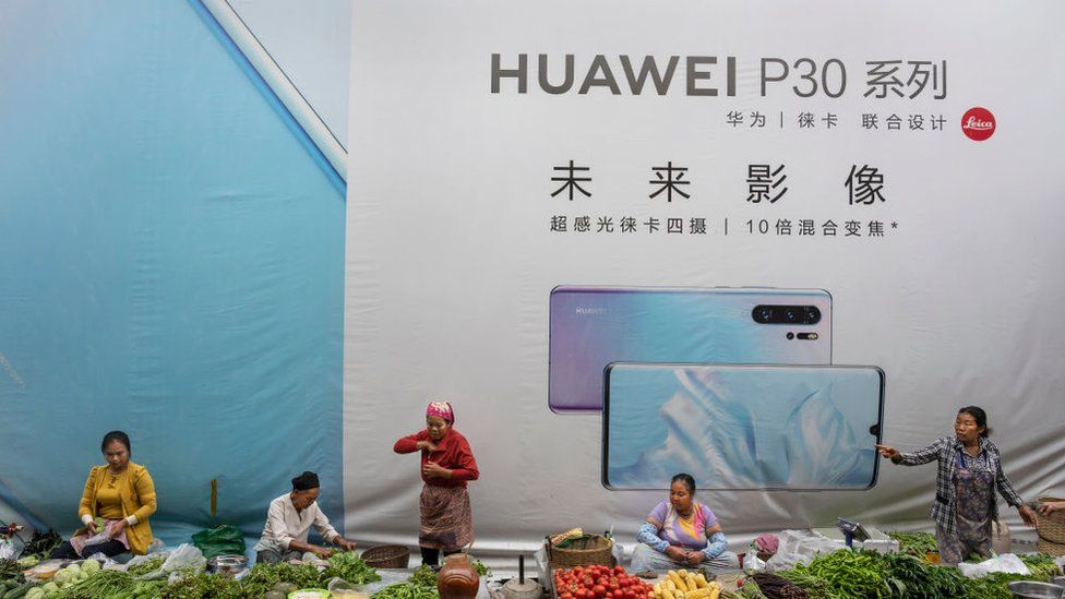 Women sell vegetables in front of a billboard advertising smartphones for China's Huawei Technologies Co., on June 1, 2019 in Mangshi, Yunnan Province, southwestern China.