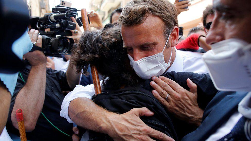 Emmanuel Macron hugs a Beirut resident