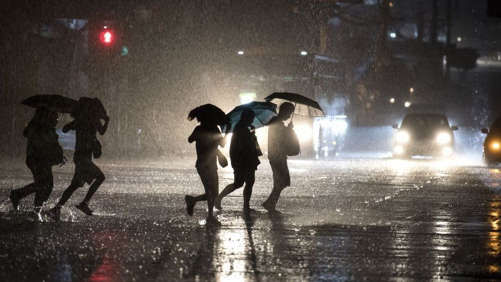 People use umbrellas as they cross a street during a heavy downpour in Manila