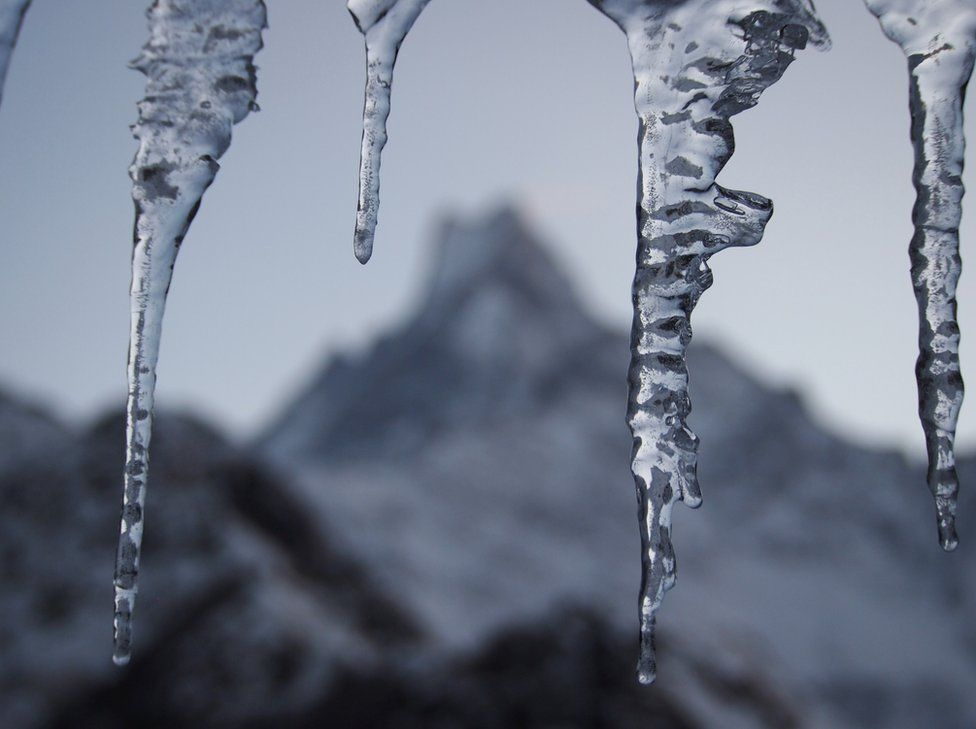 Icicles in front of a landscape