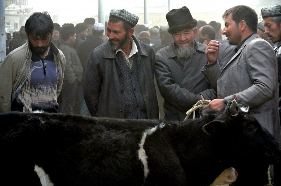 Uighur men gather at a bazaar to sell their sheep in Hotan, in the Xinjiang region