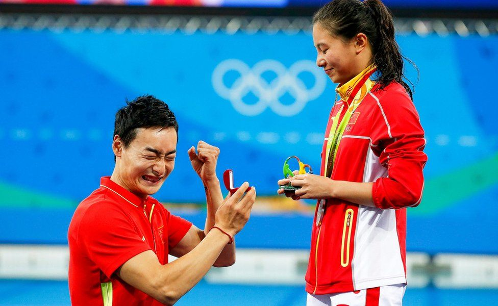 """He Zi (R) of China receives a marriage proposal from Chinese diver Ki Qin (L) after winning the silver medal in the women""""s 3m Springboard final of the Rio 2016 Olympic Games Diving events"""
