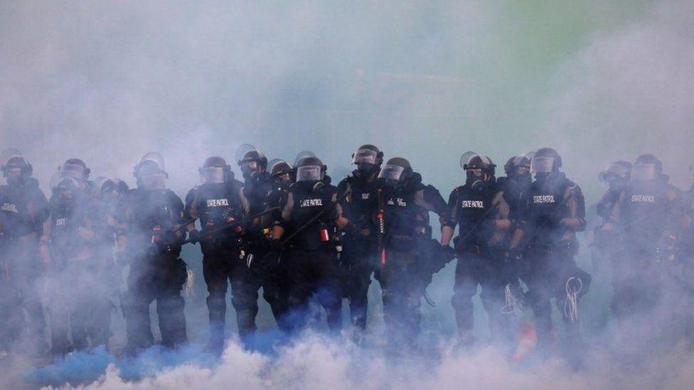 Police officers walk through tear gas in Minnesota