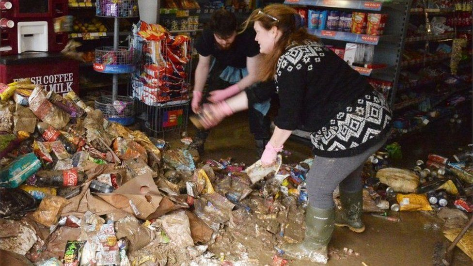 Shop workers in Cockermouth clean up flood damage