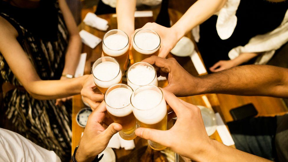 people clinking pint glasses in pub