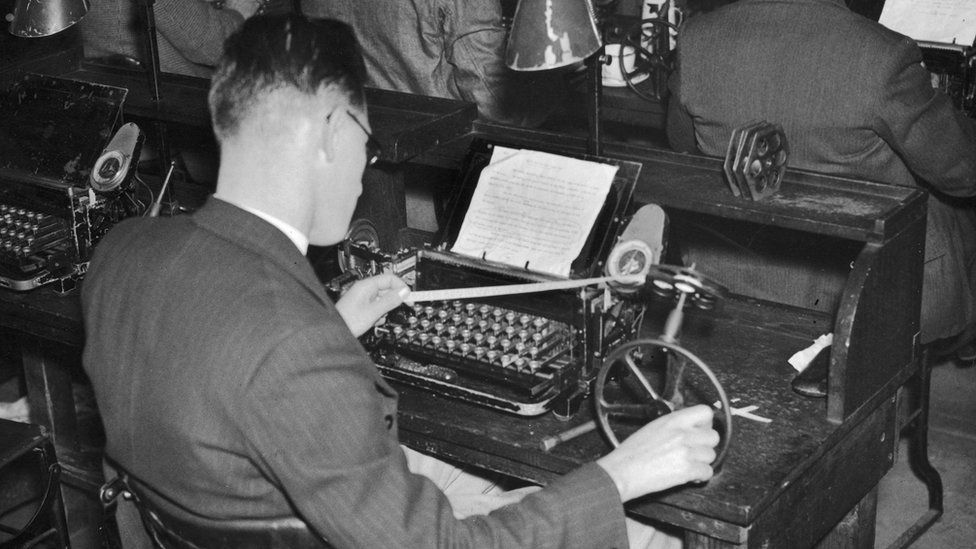 A man operating a ticker-tape machine circa 1935 in the wire room at the Daily Express building in Fleet Street, London.