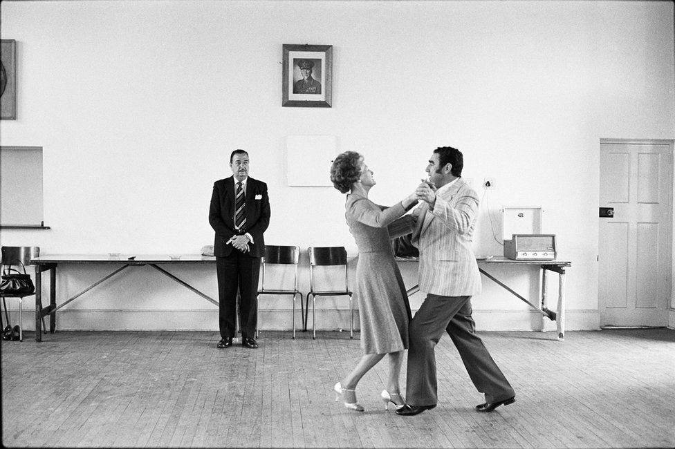 Dancing-master Ted van Rensburg watches two of his ballroom pupils, swinging to a record of Victor Sylvester and his Orchestra, in the MOTHS' Hall at the old Court House, Boksburg. 1980.