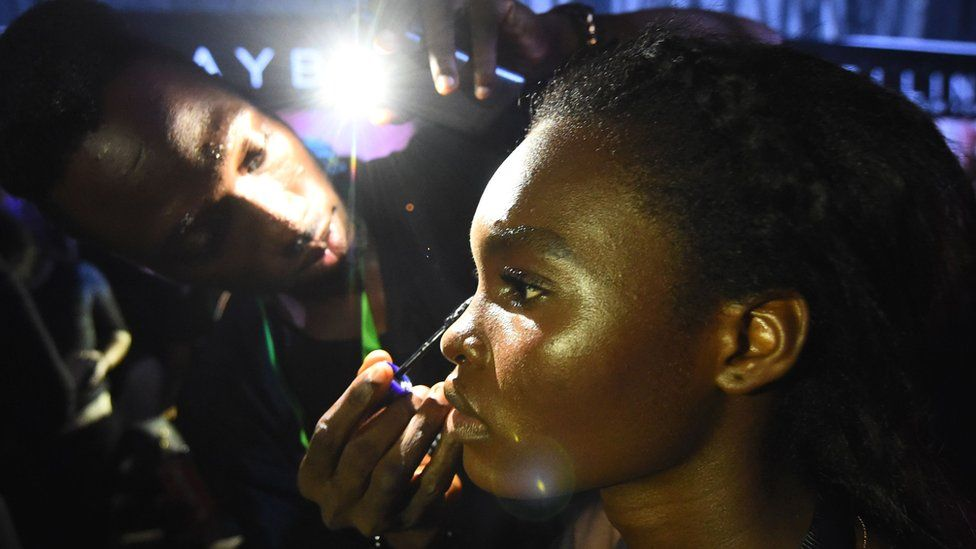 A make-up artist uses a phone's light to prepare a model following an electrical problem during the Lagos Fashion Week - 25 October 2018