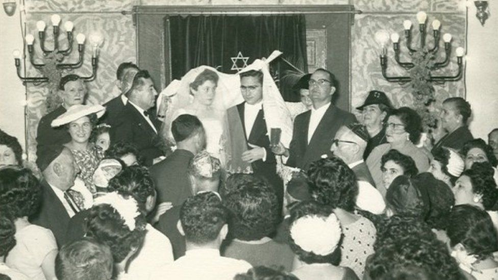 People at a wedding in a synagogue