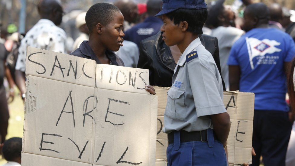 Protester in Zimbabwe holds placard calling sanctions evil