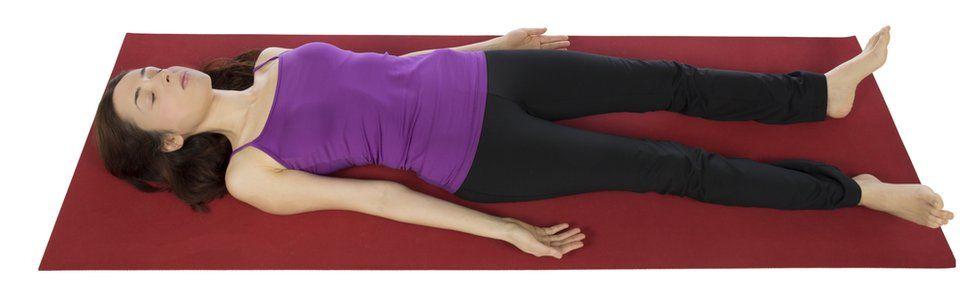 A woman lying on a yoga mat