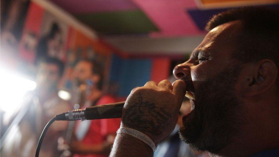 Adrian Baraldo sings into a microphone in the music studio at Punta de Rieles