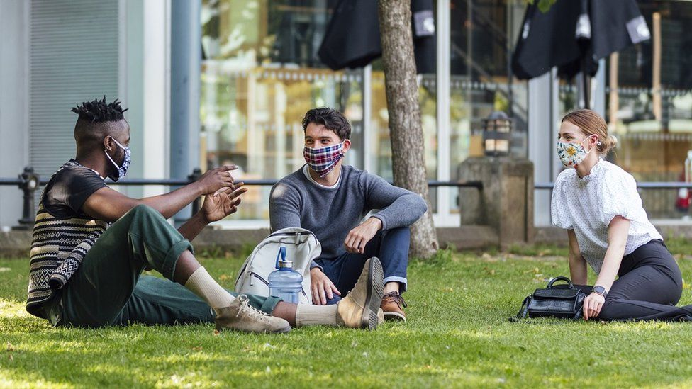 Three friends chat at a social distance while wearing face coverings